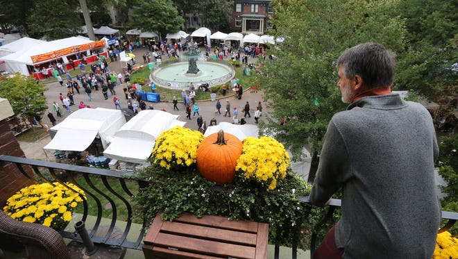 Keith Simon takes in the view from his third-floor townhouse as the St. James Art Fair in Old Louisville got underway.October 2, 2015