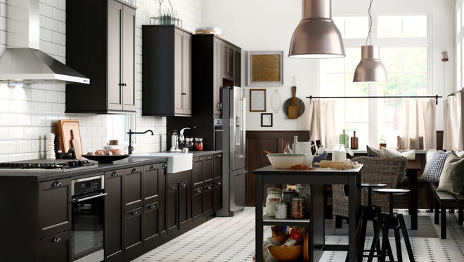 In this photo provided by Ikea, the Laxarby cabinet door has a distinctly traditional look, in a warm black-brown hue. Pairing black with metallic elements, like these big pendants, is on-trend.
