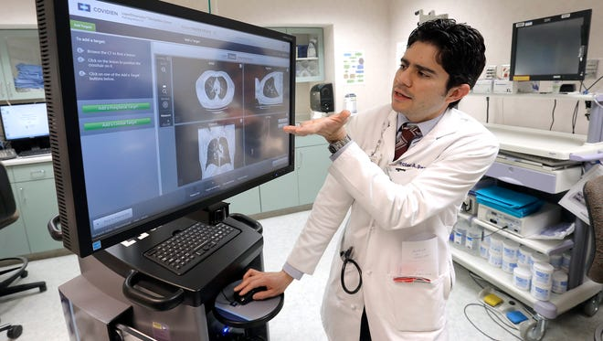 Dr. Hector Payan demonstrates a new machine that can help the detection and treatment of lung cancer. The Covidien superDimension Navigation System gives doctors turn-by-turn directions through the lungs to find abnormalities, which were previously detected by CAT scans.