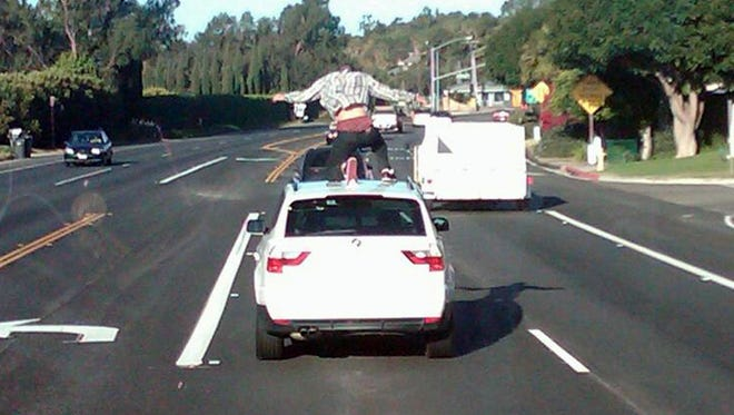 This photograph taken from a school bus May 12, 2010, shows a Malibu High School student climbing on top of a moving car in an area where the speed limit is about 50 mph.