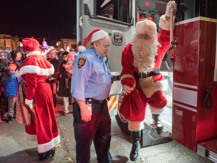 Capt. Jim Davison helps Santa Claus off of the fire