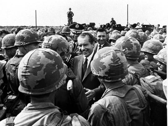 President Nixon is surrounded by combat infantrymen of the U.S. First Infantry Division at their headquarters at Di An, 12 miles north of Saigon, July 30, 1969.