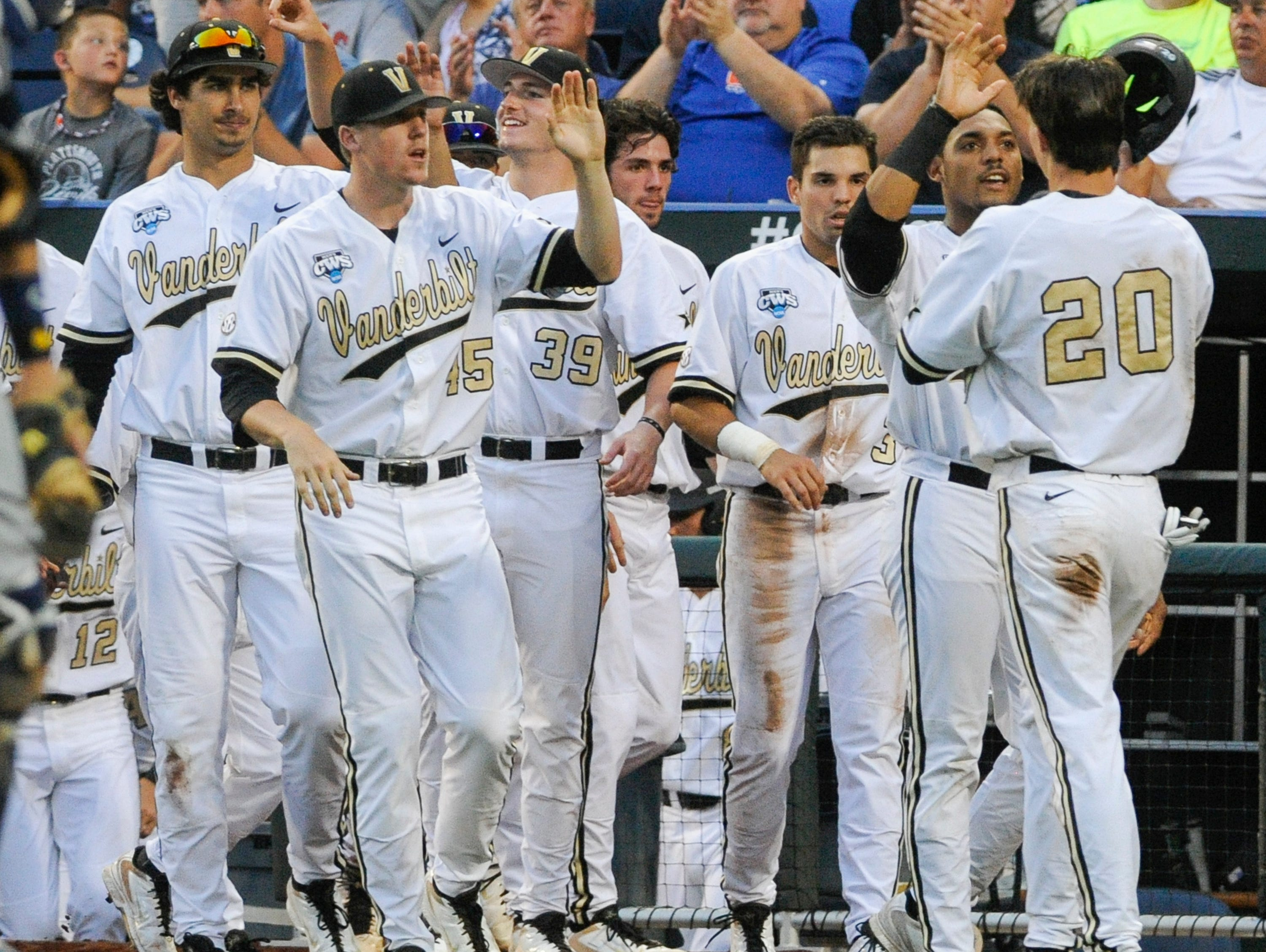 Vanderbilt's Bryan Reynolds (20) is greeted at the dugout after he scored against UC Irvine on a double by Zander Wiel in the fifth inning of an NCAA baseball College World Series game in Omaha, Neb., Monday, June 16, 2014. (AP Photo/Eric Francis)