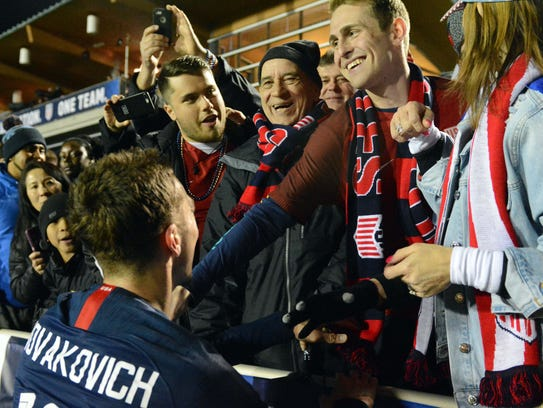 United States forward Andrija Novakovich, a Muskego native, is greeted by his family after earning his first cap during an international friendly men's soccer match against Paraguay in North Carolina on March 27. Among those on hand were (from left) cousin Nikola Prpa, grandfather Rade Prpa (in stocking cap), father Mane (partially obscured), family friend Brandon Roesch (with scarf) and mother, Zorka.