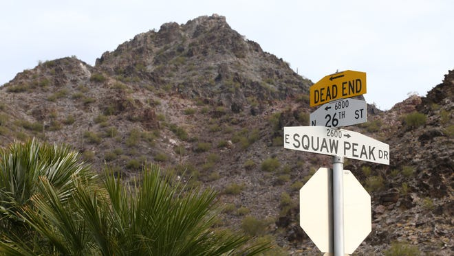 """The Squaw Peak Drive sign is seen with Piestewa Peak in the background on Jan. 3, 2017 in Phoenix, Ariz. Critics call the term """"squaw"""" racist and demeaning, while traditionalists say it simply connotes the history of the Old West."""