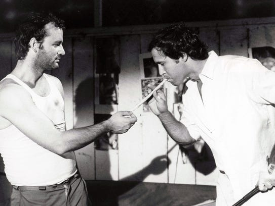 """Carl (Bill Murray) lights a """"big Bob Marley joint"""" for Ty (Chevy Chase) in a scene from """"Caddyshack."""""""