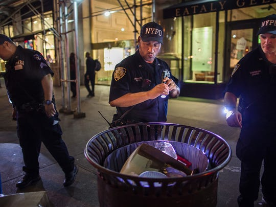 Police officers look for suspicious packages along