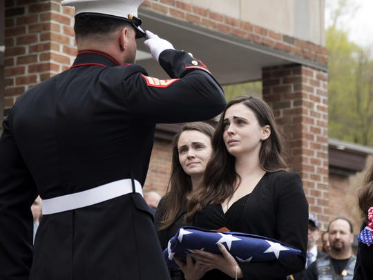 Beth Regan is presented with the flag that draped the