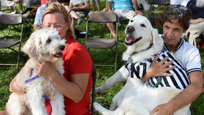 Dog lovers Ellen Homenick and Linda Perricone try to contain the excitement of Ivy and Stella.