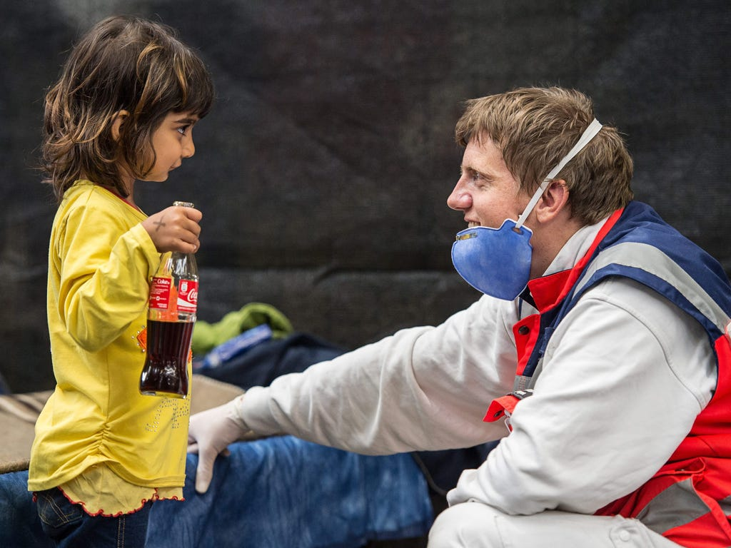 A volunteer from the German Red Cross plays with Zena, a little girl from Syria in an emergency shelter in Rottenburg, Germany.