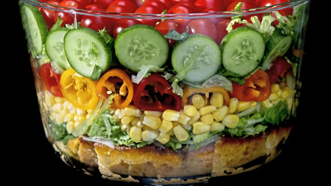 Built on a layer of savory cornbread, the summer trifle salad is made with shredded romaine lettuce, sweet corn, mini peppers, cucumbers and cherry tomatoes.