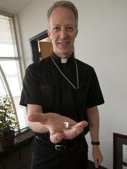 The Rev. Bill Wack shows off the ring he will wear