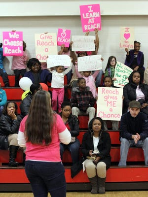Reach Academy for Girls community members listen to parent Beth Conrad during a rally in support of the charter school near New Castle, Del., that is facing closure, Thursday, Nov. 21, 2013.