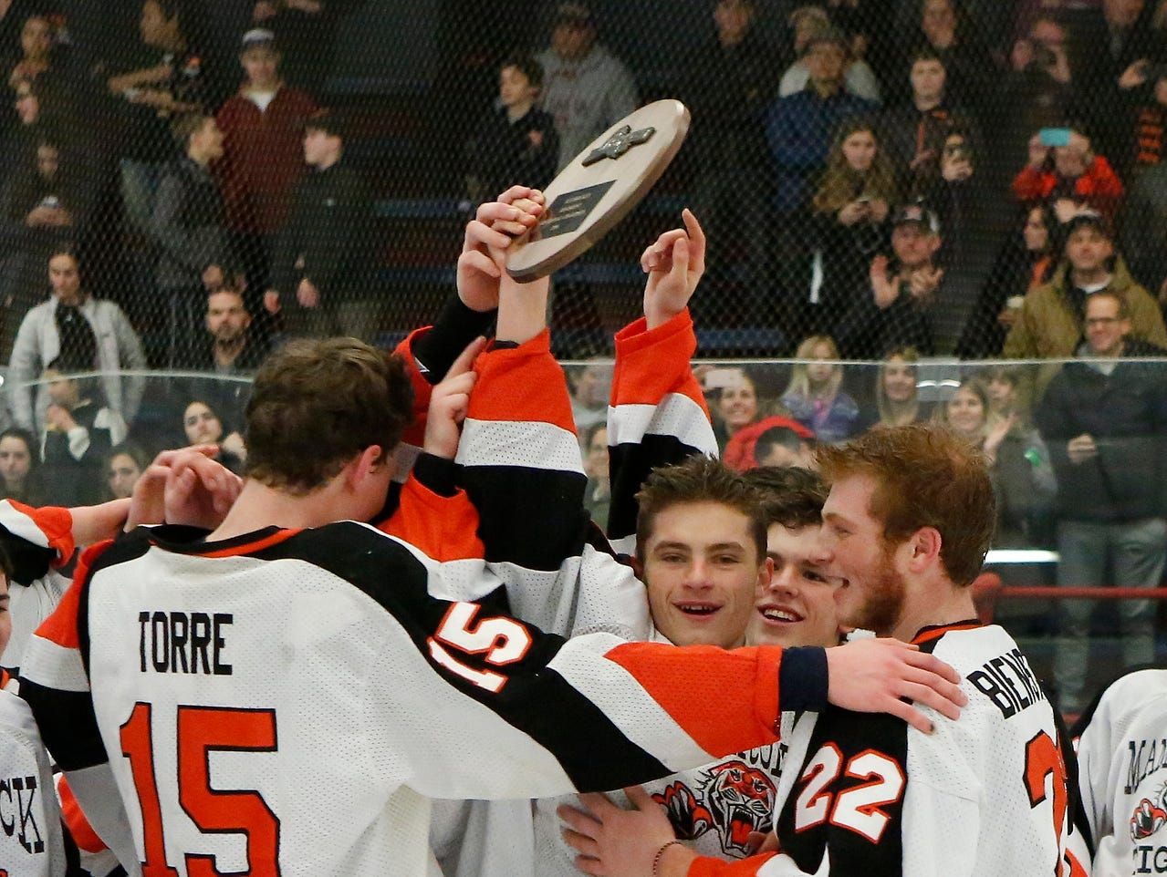 Mamaroneck's James Torre (15), Will Kirk (19) center, and Jason Bienstock (22) hold up the regional championship plaque after their 5-1 win over Massena in the division 1 regional finals at Sport-O-Rama Ice Rink in Monsey on Saturday, March 05, 2016.