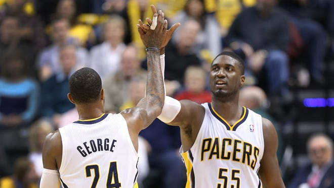 Indiana Pacers Paul George,left, highfives Roy Hibbert in the fourth quarter of their game. Indiana Pacers host the Cleveland Cavaliers Wednesday, December 31m 2013, afternoon at Bankers Life Fieldhouse.