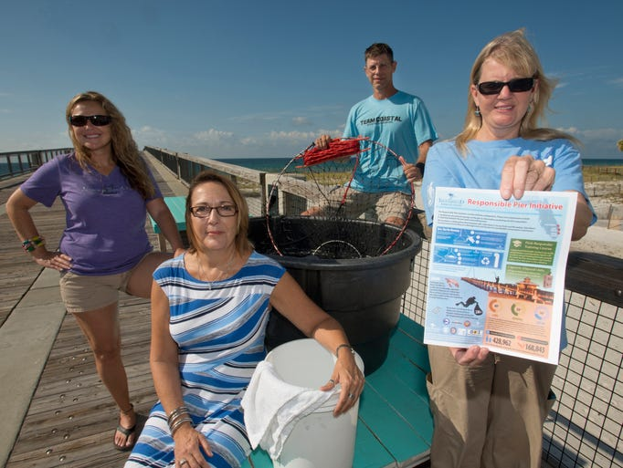 Cathy Holmes with the Navarre Beach Sea Turtle Conservation Center, right, and Navarre Pier employee, Stephanie Maddox, left, Donna Faulk, left center, and Brad Helwig, are helping to make the South Santa Rosa County pier â??marine lifeâ? friendly. As part of the new Sea Turtle Pier Initiative, they have attended training and they have attached signage to Navarre pier with instructions on what to do if an angler hooks a sea turtle.