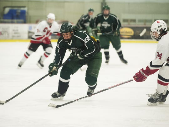 Rice's Cam Cousino (22) skates past CVU's Oscar Kelly (24) with the puck during the boys hockey game between the Rice Green Knights and the Champlain Valley Union Redhawks at Cairns Ice Rink on Feb. 4 in South Burlington.