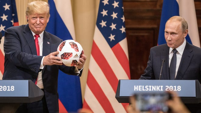 President Donald Trump (left poses with a football given to him by Russian President Vladimir Putin during a joint press conference after their summit on July 16, 2018 in Helsinki, Finland.