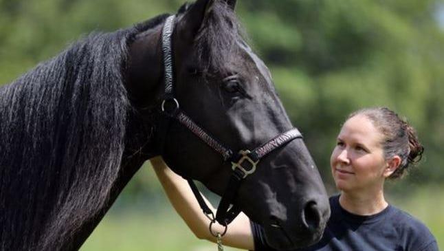 Tawnee Preisner, founder of Horse Plus Humane Society, pets Skywalks Magical Dream on Sept. 13, 2016.