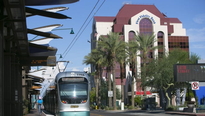 A woman gets off the eastbound light rail at the light rail station along Main Street and Center Street in downtown Mesa on Wednesday, August 26, 2015.