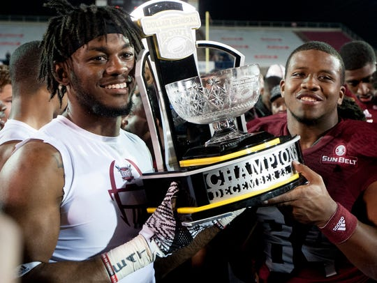 Troy University players carry the champions trophy