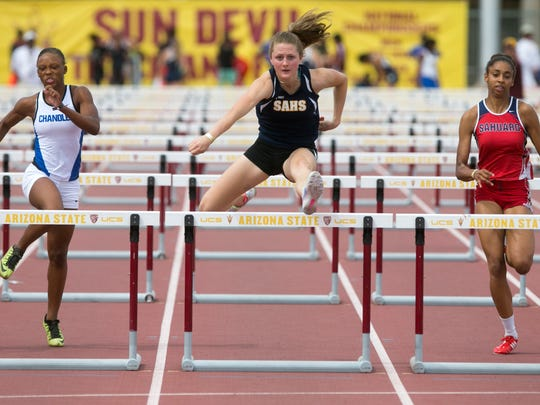 Summit Academy's Elsja Mecham (center) leads Arniesha Mitchell (left) of Chandler High and Brielle Sterns of Sahuaro High during the girls high school 100 meter hurdles during the Sun Angel Classic track & field meet at Sun Angel Stadium in Tempe on April 11, 2015. Mecham won the event.
