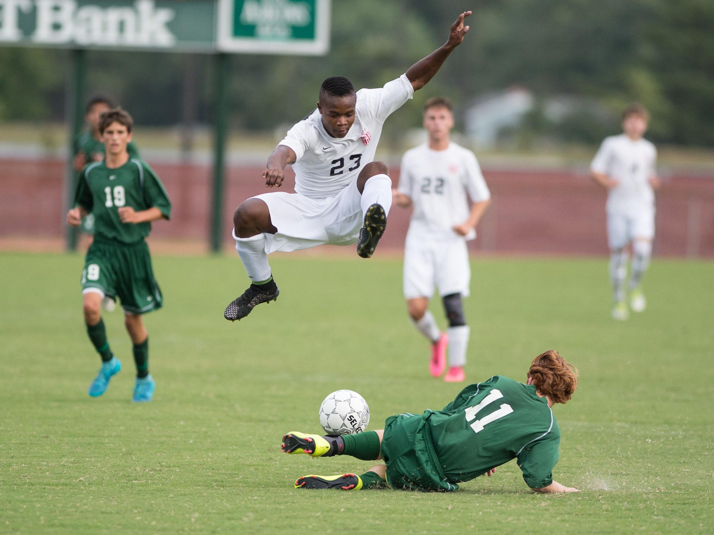 JMB's Cermy Oneus leaps over Parkside's Max Corry after a slide tackle.
