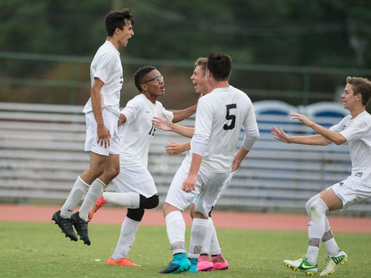 JMB's Mahdi Fotouhi, left, celebrates with teammates after scoring a goal.