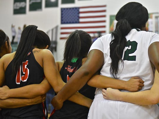 Members of the Lakota West and Mason girls basketball teams embrace during the National Anthem.
