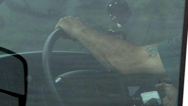 A motorist is seen using a cell phone while driving along Route 684 in Somers.