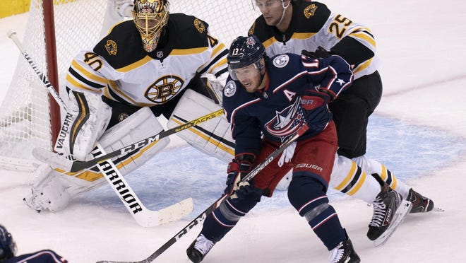 Blue Jackets right wing Cam Atkinson battles for position with Boston Bruins defenseman Brandon Carlo (25) in front of Bruins goaltender Tuukka Rask during the first period.