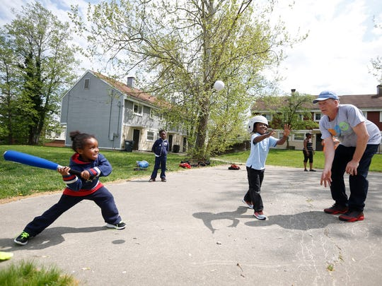 Daniel Harper, 5, plays baseball with Mike Gramann
