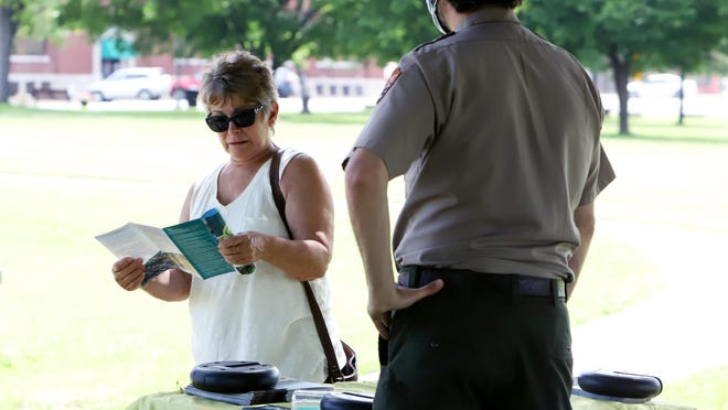 Sharon Pennington talks with Fort Smith National Site Ranger Loren McLane about the outdoor areas that are now open to the public, Monday, June 1, 2020, that include the grounds, gallows and commissary.