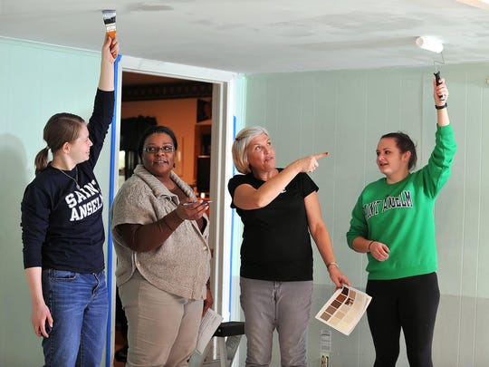 Saint Anselm College students Brittney Taylor, 22, of North Hanover, Mass. (left), and Vanessa Burton, 21, of Colchester, Conn. (right), volunteer painting the dining room at Elwyn's Baywood group home in Vineland, while Elywn employees Berlinda Scurry (second from left) and Susan Sauro (second from right) help, as a part of a service project for the college with Cumberland County Habitat for Humanity, Tuesday, Jan. 12.