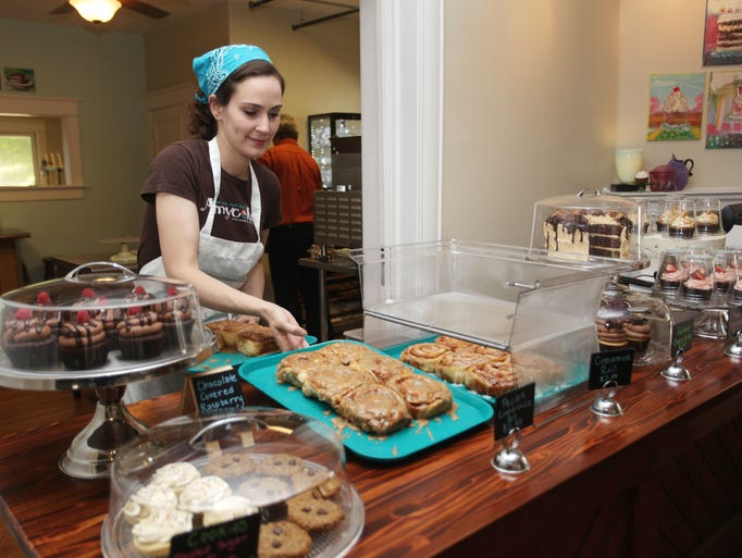Amycakes owner Amy Bloodworth sets out a fresh tray of maple pecan cinnamon rolls on Thursday, August 14, 2014. Amycakes Bakery has moved to a historic house on Walnut Street and now offers an assortment of ready-made treats.