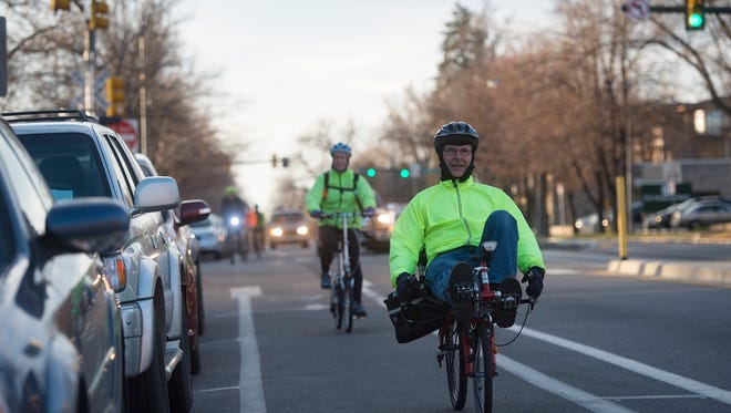 Todd Block rides his bicycle down Mason Street during Winter Bike to Work Day on Wednesday, December 13, 2017. Stations around Fort Collins offered breakfast or bike maintenance to cyclists on their way to work.