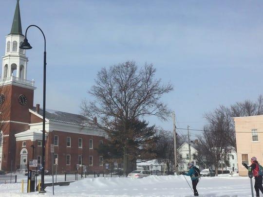 Skiers Cayla Hannaker, center, and Louisa Jerome ply Pearl Street sidewalks in Burlington on Jan. 13, 2018.