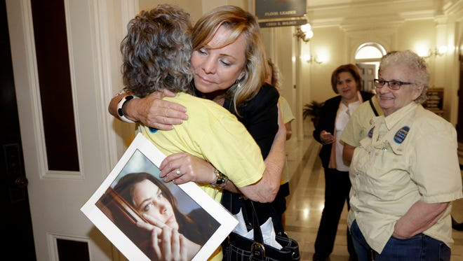 Debbie Ziegler holds a photo of her late daughter, Brittany Maynard, as she receives congratulations from Ellen Pontac, left, after a right-to die measure was approved by the state Assembly in Sacramento, Calif, on Sept. 9, 2015.