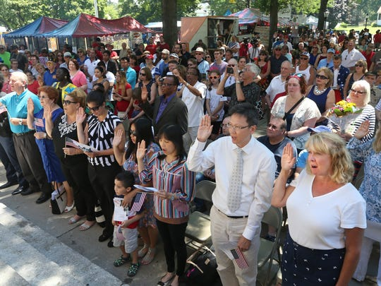 Laura Breed, Fairport, a native of Canada, front row far right, joins with 14 others in raising her hand and taking an oath of citizenship at the Naturalization Ceremony for new citizens of the United States held Tuesday, July 4, on the front steps of Irondequoit Town Hall.