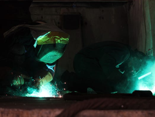 Welders David Smith and Travis Hare repair a truck