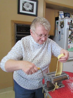 Using her friend's pasta machine, Susan Manzke cranks out her first batch of homemade noodles.
