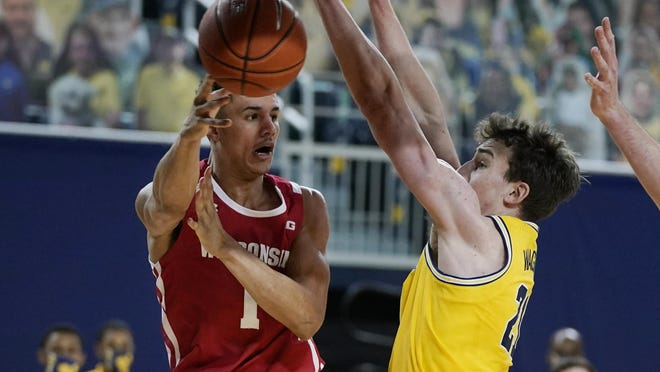 Wisconsin guard Jonathan Davis (1) passes around Michigan guard Franz Wagner (21) during the first half of an NCAA college basketball game, Tuesday, Jan. 12, 2021, in Ann Arbor, Mich.