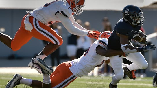 Rice running back Samuel Stewart, right, is tackled