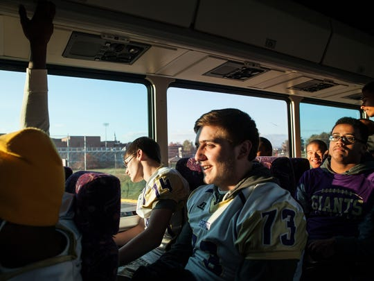 Waynesboro's Luke Gibson, center, sits with fellow teammates as they arrive at the football field before the start of their Group 3A first round playoff game against Hidden Valley in Roanoke on Friday, Nov. 14, 2014.