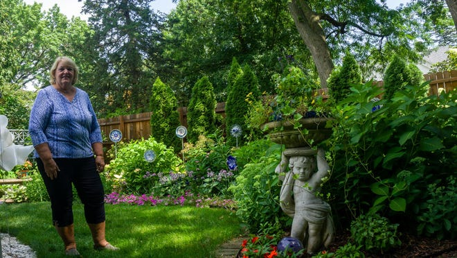 Judy Singer stands alongside one of her numerous garden statues on Monday afternoon.