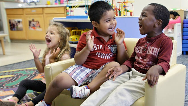 From right, Errol McKinson, Carlos Granados and Lila Munoz enjoy a sing-along at the Early Head Start program in Woodbourne, N.Y., on July 23, 2013. Sullivan County Head Start has cut enrollment and staff in response to the sequester.