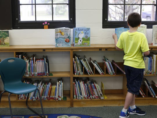 A young student looks over books in the media center