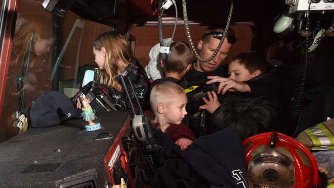 Farmington Fire Department Capt. Brian Balfour shows his kids one of the engines during the grand opening of the department's Station 1 on Wednesday at North Auburn Avenue and West La Plata Street.