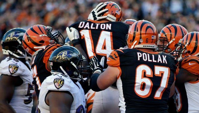 The Bengals crowd around QB Andy Dalton after his decisive TD on Sunday.
