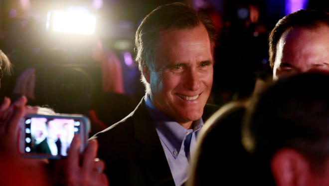 Mitt Romney is greeted by fellow Republicans at the Republican National Committee's Annual Winter Meeting aboard the USS Midway on Jan. 16, 2015, in San Diego.